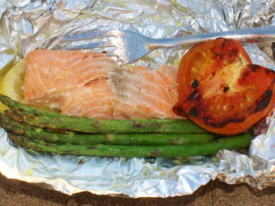 Beach barbecued lemon infused salmon with griddled tomato and asparagus.