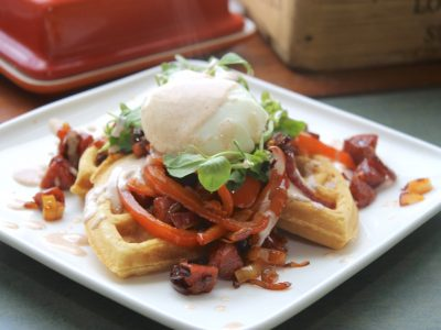 Breakfast waffles topped with chorizo, fried peppers, a runny poached egg and paprika yoghurt